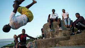 A group of kids pulls stunts off the steps leading to Alki Beach on July 15, 2016.