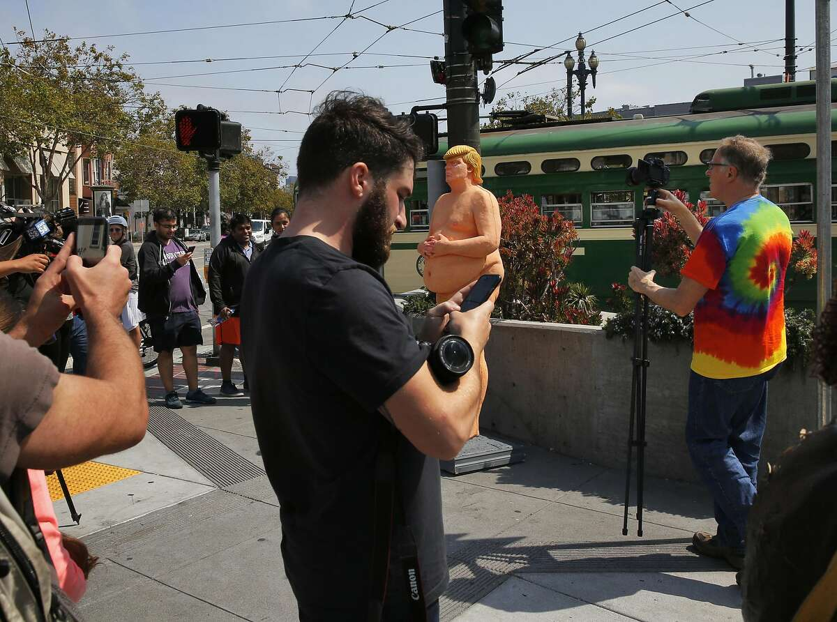 """People crowd around a nude statue of Republican Presidential Nominee Donald J. Trump to take photographs of it on Market and Castro streets August 18, 2016 in San Francisco, Calif. Written at the feet of the statue says """"the emperor has no balls"""" -Indecline"""