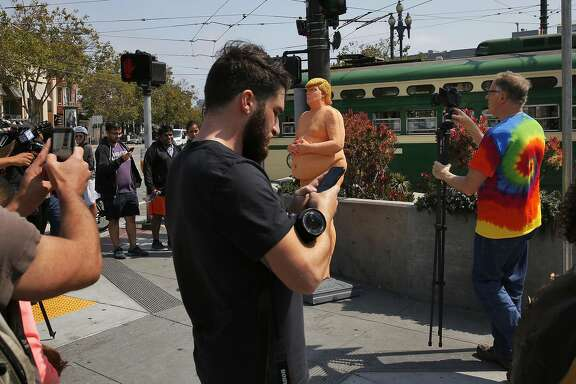 "People crowd around a nude statue of Republican Presidential Nominee Donald J. Trump to take photographs of it on Market and Castro streets August 18, 2016 in San Francisco, Calif. Written at the feet of the statue says ""the emperor has no balls"" -Indecline"