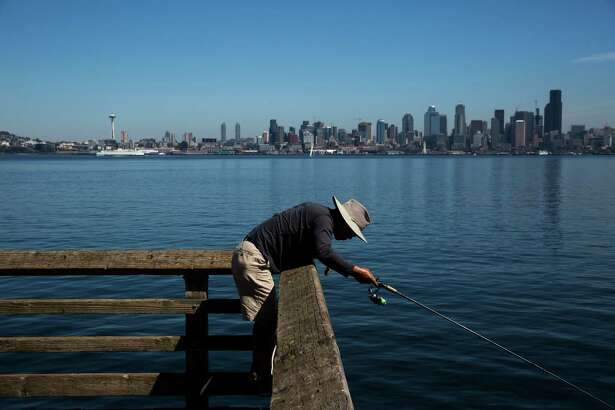 A man fishes for King salmon off the pier at Alki Point on Aug. 16, 2016.