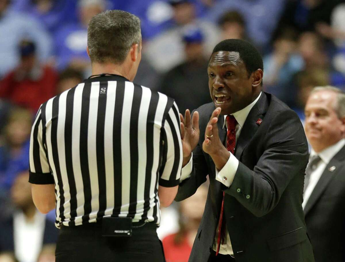 Alabama head coach Avery Johnson, right, argues a call with an official during the first half of an NCAA college basketball game against Kentucky in the Southeastern Conference tournament in Nashville, Tenn., Friday, March 11, 2016.