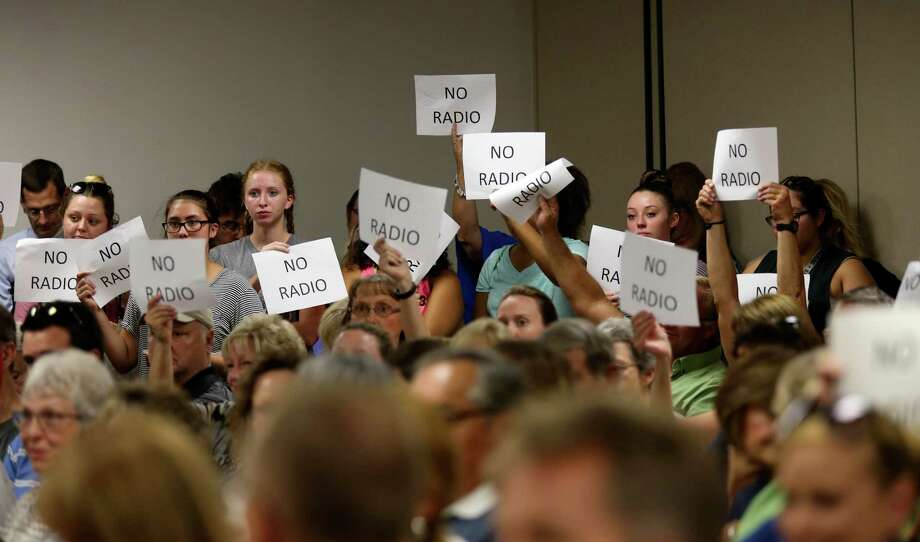 Signs are raised against a proposed partnership between he Sequin Independent School District and Guadalupe Media, LTD, during a SISD Special Meeting, Thursday, August 18, 2016. The partnership would let the district operate KWED radio station and also a free local daily newspaper. After meeting in executive session, the board came out and voted 6-1 in favor of negotiating with the company for the partnership. Photo: JERRY LARA, Staff / San Antonio Express-News / © 2016 San Antonio Express-News