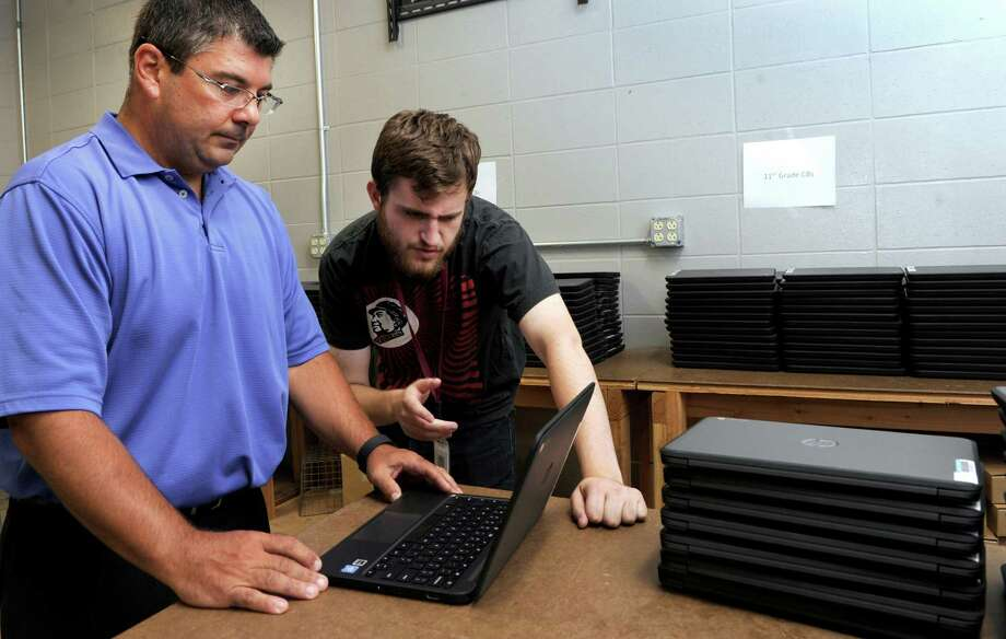 Chris Troetti, left, principal of Bethel High School, talks with Evan Gorry, an IT technician with the Bethel Public Schools about the new chromebooks - 900 in all - that will be given out to students this year. Photo Thursday, August 18, 2016. Photo: Carol Kaliff / Hearst Connecticut Media / The News-Times