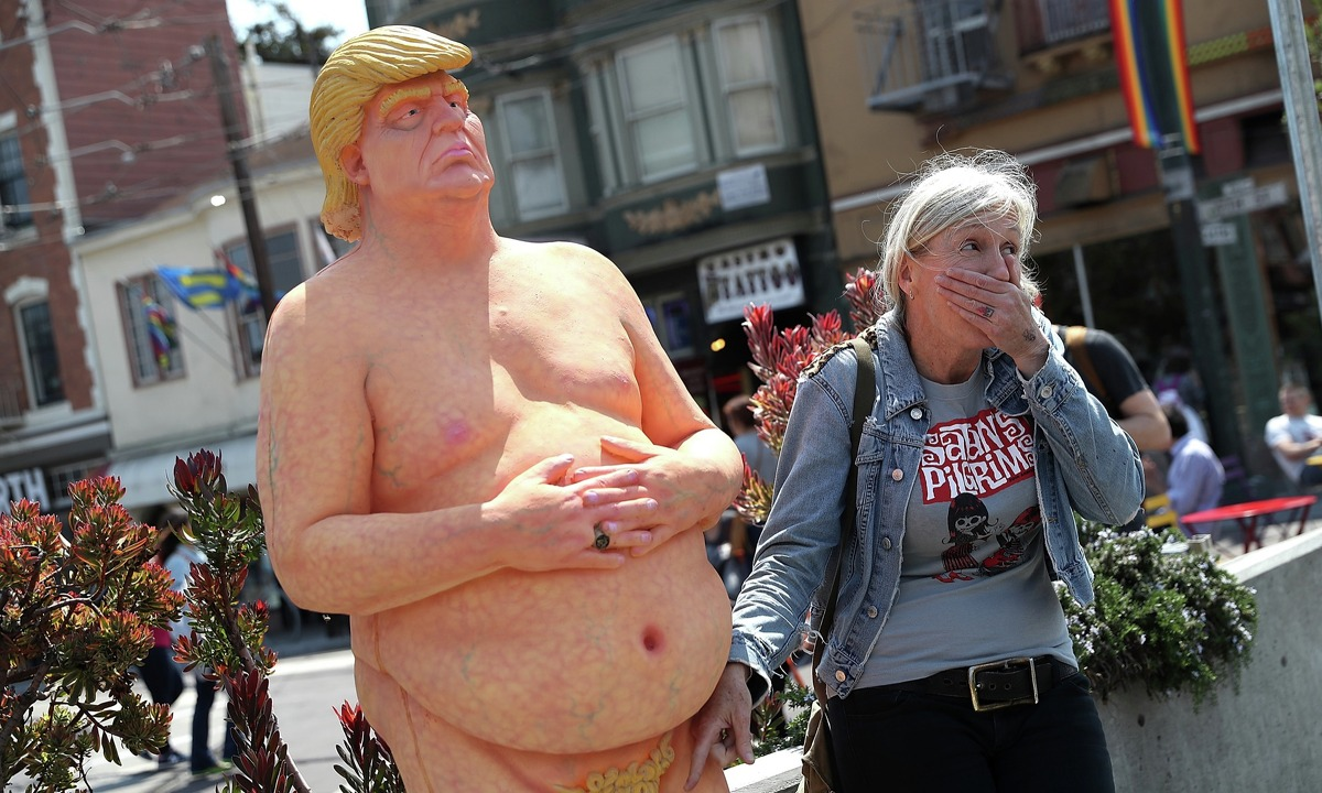 A passerby has a picture taken with a statue depicting republican presidential nominee Donald Trump in the nude on August 18, 2016 in San Francisco, United States. Anarchist collective INDECLINE has created five statues depicting Donald Trump in the nude and placed them in five U.S. cities on Thursday morning. The statues are in San Francisco, New York, Los Angeles, Cleveland and Seattle.