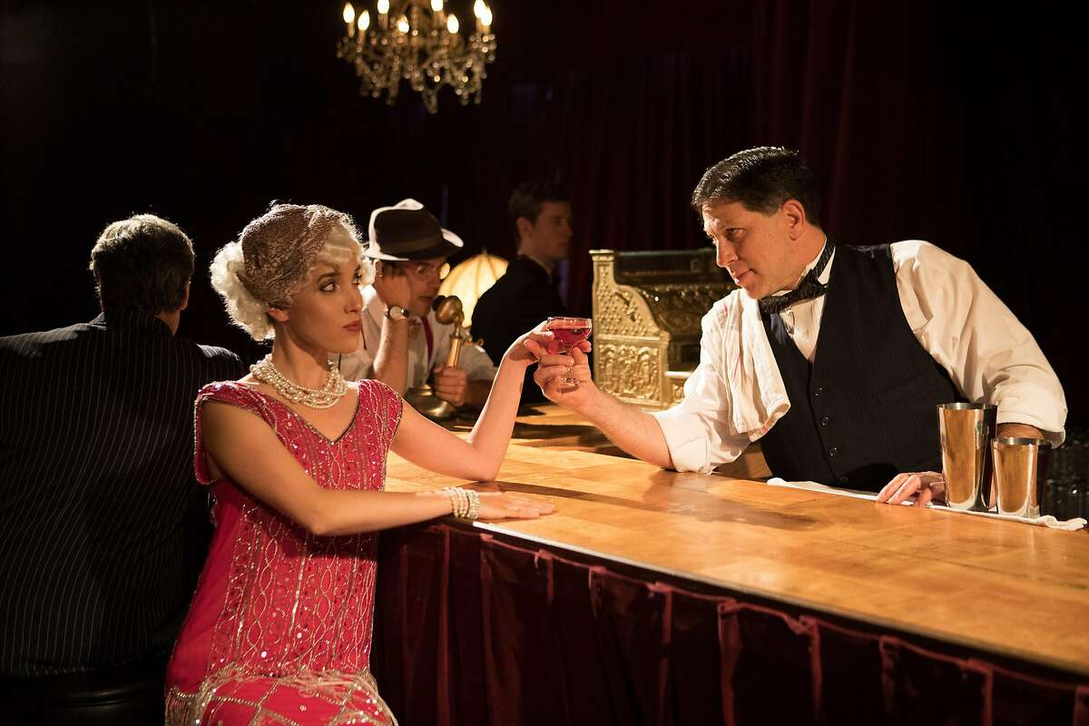 A flapper (Jessica Waldman) orders a drink from the bartender (Rick Roiting).