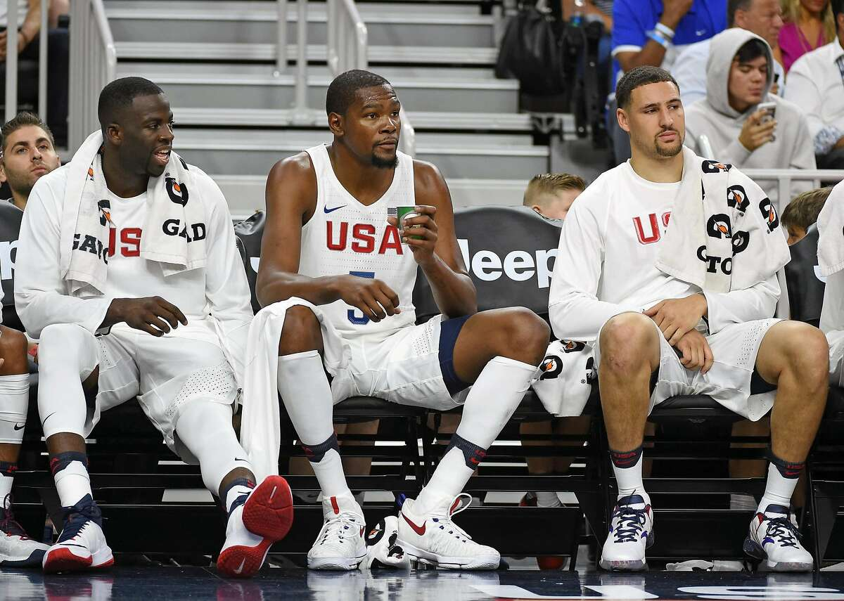 LAS VEGAS, NV - JULY 22: (L-R) Draymond Green #14, Kevin Durant #5 and Klay Thompson #11 of the United States sit on the bench during a USA Basketball showcase exhibition game against Argentina at T-Mobile Arena on July 22, 2016 in Las Vegas, Nevada. The