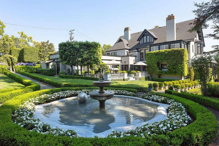A stately fountain provides the centerpiece to a verdant landscape lined with box hedges.