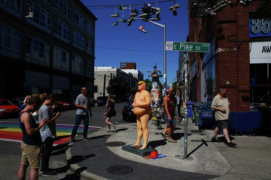 Passers-by interact with a life-size statue of a naked Republican Presidential candidate Donald Trump, that appeared on the corner of 11th and E Pike Street in Capitol Hill, Thursday, Aug. 18, 2016. Identical statues appeared in Los Angeles, New York, San Francisco, and Cleveland and are the brainchild of INDECLINE, an activist collective. Photo: GENNA MARTIN, SEATTLEPI.COM / SEATTLEPI.COM