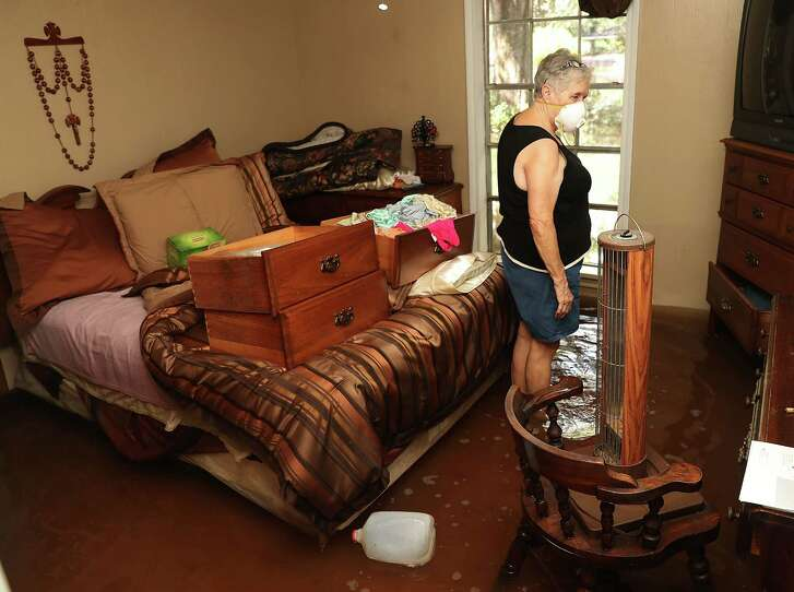Elsie Lazarus salvages what she can Thursday from the bedroom of her flooded home in St. Amant, La. Last week Louisiana was overwhelmed with flooding that caused at least 13 deaths and damaged thousands of homes in a disaster eerily reminiscent of Hurricane Katrina.