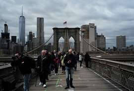 Tourists walk across the Brooklyn Bridge in New York on May 5, 2016. / AFP / Jewel SAMAD        (Photo credit should read JEWEL SAMAD/AFP/Getty Images)