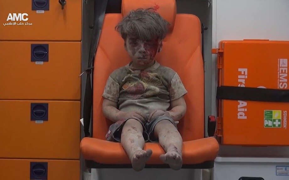 In this frame grab taken from video provided by the Syrian anti-government activist group Aleppo Media Center, a child sits in an ambulance after being pulled out of a building hit by an airstrike, in Aleppo, Syria, on Wednesday. Omran Daqneesh, 5, was pulled from the damaged building and the video exploded around the world on social media Photo: HOGP / Aleppo Media Center