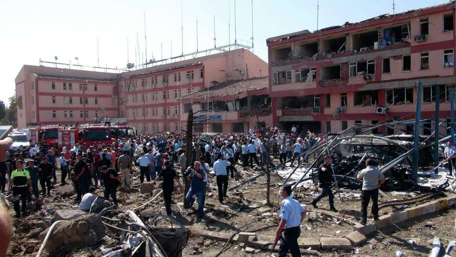 Turkish authorities search outside a damaged building after an explosion in Elazig, eastern Turkey, on Thursday, Aug. 18, 2016. Two car bombings targeted police stations in Turkey, killing a number of people and wounding hundreds, officials said Thursday. Turkish authorities have banned distribution of images relating to the Elazig explosion within Turkey.(Sahismail Gezici/DHA via AP) Photo: Sahismail Gezici, STR / DHA