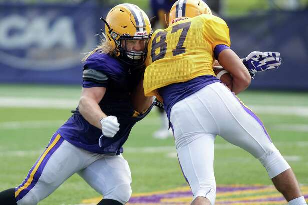 University at Albany football player Michael Nicastro, left, tackles a teammate during practice on Wednesday, Aug. 17, 2016, in Albany, N.Y.  (Paul Buckowski / Times Union)