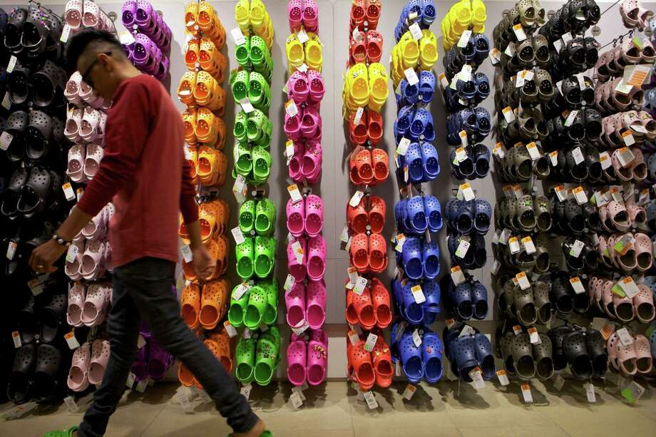 """FILE - In this April 9, 2010, file photo, Summett Kumar, a Crocs ambassador, works at Crocs store inside the Beverly Center shopping mall in Los Angeles. A Texas couple is suing footwear maker Crocs and a Waikiki resort after their 2-year-old son's foot got caught in an escalator while the family visited Hawaii in 2014 for an oral surgeon convention. According to the lawsuit, the escalator """"completely de-gloved"""" the toddler's left foot, requiring emergency surgery. (AP Photo/Damian Dovarganes, File) Photo: Damian Dovarganes, STF / Copyright 2016 The Associated Press. All rights reserved. This material may not be published, broadcast, rewritten or redistribu"""