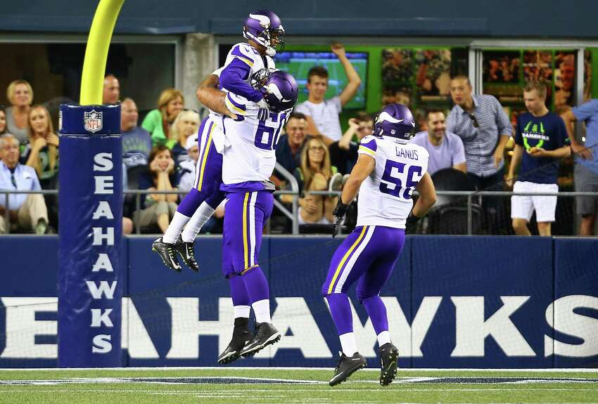 Minnesota's Carter Bykowski (60) and Jake Ganus (56) congratulate Marcus Sherels on his interception and touchdown in the fourth quarter of the Seahawks vs. Vikings pre-season game at CenturyLink Field, Thursday, Aug. 18, 2016.