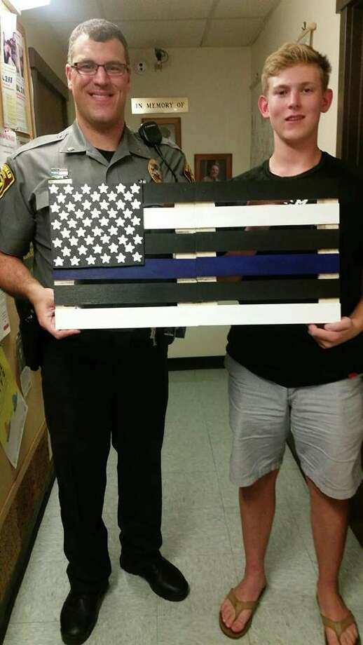 Patrick Ogden, right, presented the Ridgefield Police Department with a flag he made. Photo: Contributed Photo / Contributed Photo