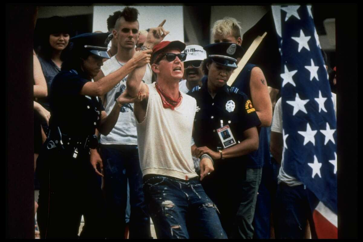 Police officers restrain Gregory Johnson after his flag-burning demonstration to express anger against Reagan policies during the Republican National Convention in 1984. Johnson was arrested and his case went all the way to the Supreme Court. Keep going for a look at other times Texas cases have gone to the highest court in the land.