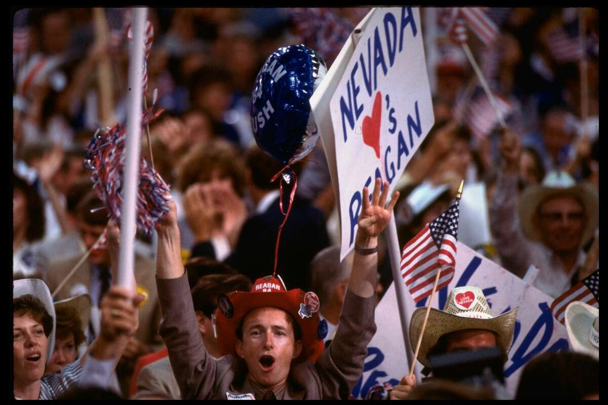 NEVADA LOVES REAGAN sign framing enthused Reagan/Bush supporter with campaign-sloganed cowboy hat, on delegate-crowded Republican National convention floor. (Photo by Bill Pierce/The LIFE Images Collection/Getty Images)