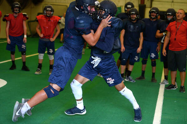 Hardin-Jefferson players practice blocking down field in their indoor practice facility on Wednesday afternoon. The small building allows them to run formations when the weather is bad.  Photo taken Wednesday 8/17/16 Ryan Pelham/The Enterprise