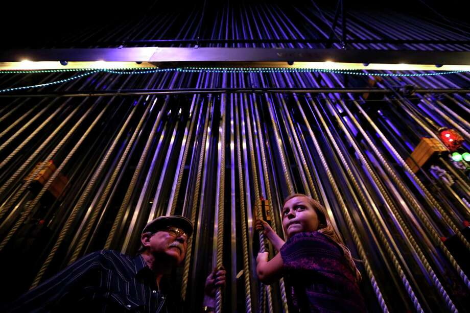 """Mike Grawl, house carpenter, instructs Shelby Murchison, 9, of Tomball, raise a 150-pound curtain along one of the ninety-seven counter weight line sets used for lowering and raising scenery back stage in the Brown Theater at the Wortham Theater Center during the 22nd Annual TransCanada Theater District Open House Sunday, Aug. 30, 2015, in Houston. This annual event marks the kick-off of the Fall performing arts season in Houston, and is a one-day-only opportunity to experience the energy and excitement of Houstoné¢Ã©""""é´s Theater District. ( Gary Coronado / Houston Chronicle ) Photo: Gary Coronado, Staff / © 2015 Houston Chronicle"""
