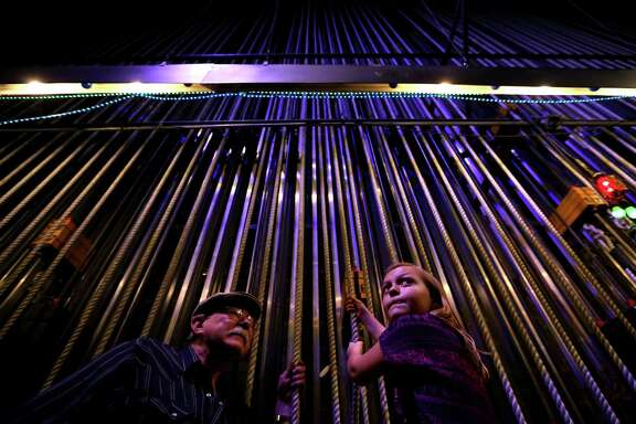 """Mike Grawl, house carpenter, instructs Shelby Murchison, 9, of Tomball, raise a 150-pound curtain along one of the ninety-seven counter weight line sets used for lowering and raising scenery back stage in the Brown Theater at the Wortham Theater Center during the 22nd Annual TransCanada Theater District Open House Sunday, Aug. 30, 2015, in Houston. This annual event marks the kick-off of the Fall performing arts season in Houston, and is a one-day-only opportunity to experience the energy and excitement of Houstoné¢Ã©""""é´s Theater District. ( Gary Coronado / Houston Chronicle )"""