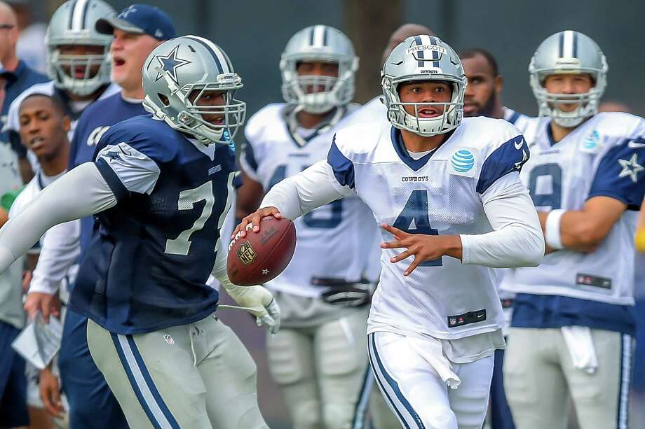 Dak Prescott (4), eluding the rush from Lawrence Okoye during a training camp scrimmage, will be vying to become the Cowboys' backup quarterback to star Tony Romo (far right in background). Photo: Gus Ruelas /Associated Press / FR157633 AP