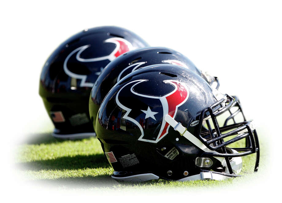 Texans helmets sit on the pracitce field during morning training camp practice at the Methodist Training Center in Houston. Photo: Bob Levey /Getty Images / 2011 Bob Levey