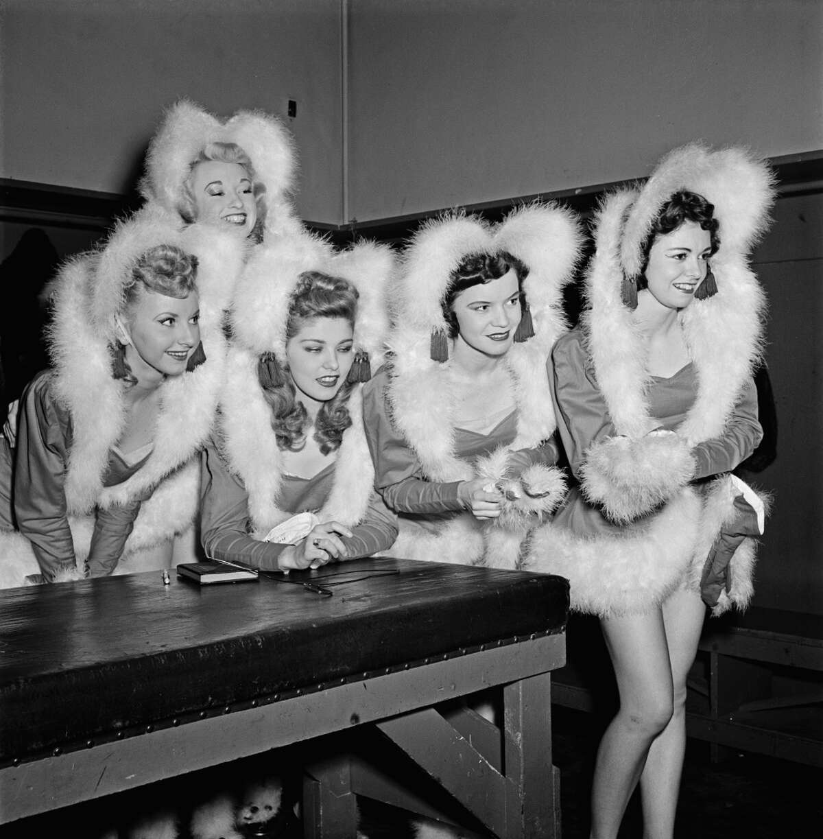 Members of The Rockettes precision dance company backstage at the Radio City Music Hall in Manhattan, New York City, circa 1950. They are wearing fur-trimmed costumes for a Christmas show. On the far right is dancer Gloria O'Malley.
