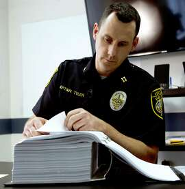 "Littleton Police Department Capt. Chris Tyler looks though the file of convicted drug dealer Mike Millette at the police station in Littleton, N.H., on Wednesday, June 1, 2016. On the growing drug problem, ""If you asked me when the epidemic first started, I would have said, �Arrest everybody.� But now looking at the magnitude of the problem and having a better understanding of it, treatment and rehabilitation are the better solutions."" (AP Photo/Jim Cole)"
