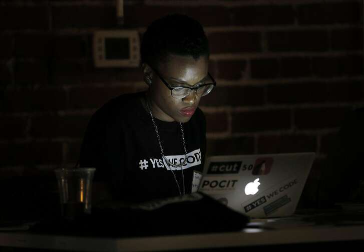 Tamyra Walker with Yes We Code, works on her laptop in the dark before her presentation during Hack the Hood, Hidden Genius Project event at Impact Hub in Oakland, Calif., on Thursday, August 18, 2016. The program places tech-savvy teens  with small business partners for the summer and helps them advance their tech skills in a real-world environment for three months.