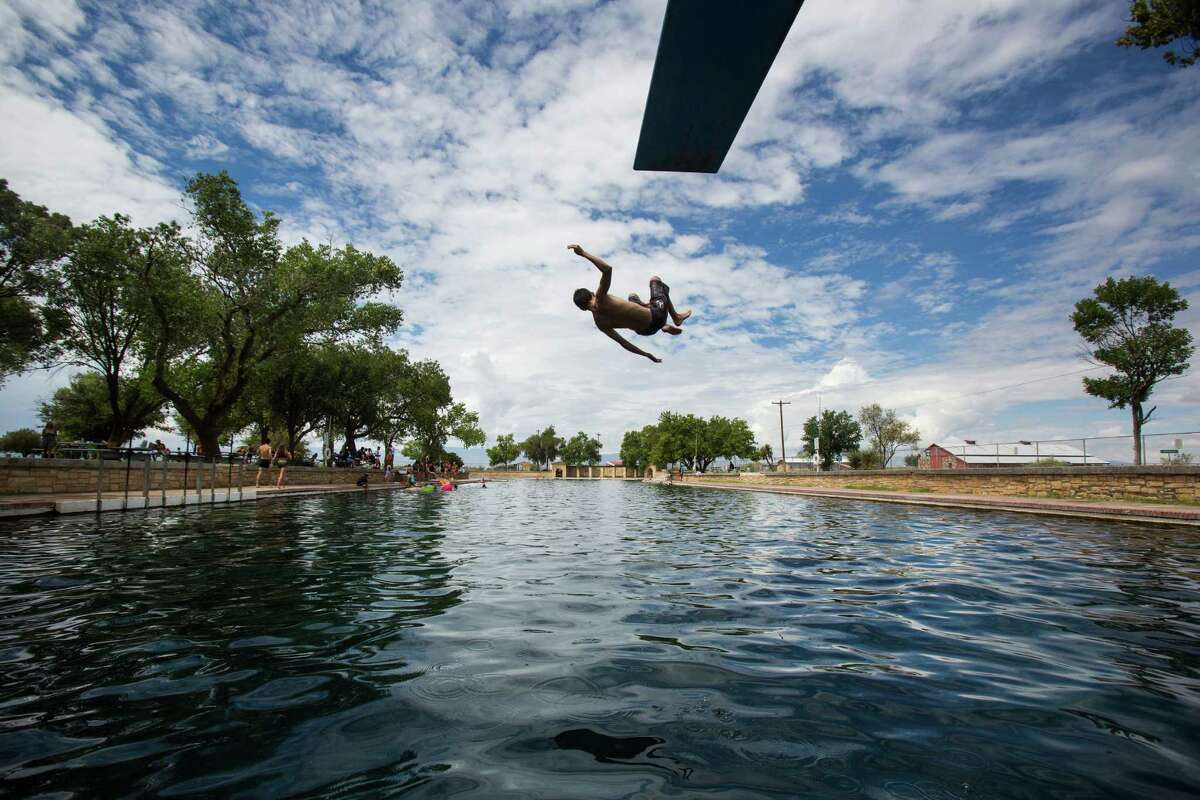 A boy jumps off the diving board into 30 feet of water at the natural spring pool at the Balmoreah State Park on Thursday, August 18, 2016. The rise of fracking nearby the town has some community members worried about their drinking water and natural springs, which serve as a popular tourism destination helping drive the town's economy.