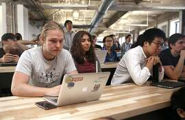 Students Christopher Pruijsen (left), Zohar Sanchez (middle), and Carl Chen (right) are some of the eighty students in their tenth month at Hack Reactor, a leading computer coding camp, listening to a lecture on Thursday, August 18, 2016, in San Francisco, Calif.