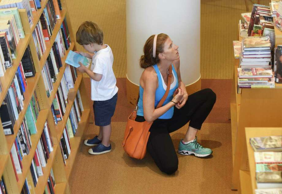 Dean, 3, and Stephanie Esquenazi, of Greenwich, browse the shelves for books at Greenwich Library in Greenwich, Conn. Thursday, Aug. 18, 2016. Photo: Tyler Sizemore / Hearst Connecticut Media / Greenwich Time