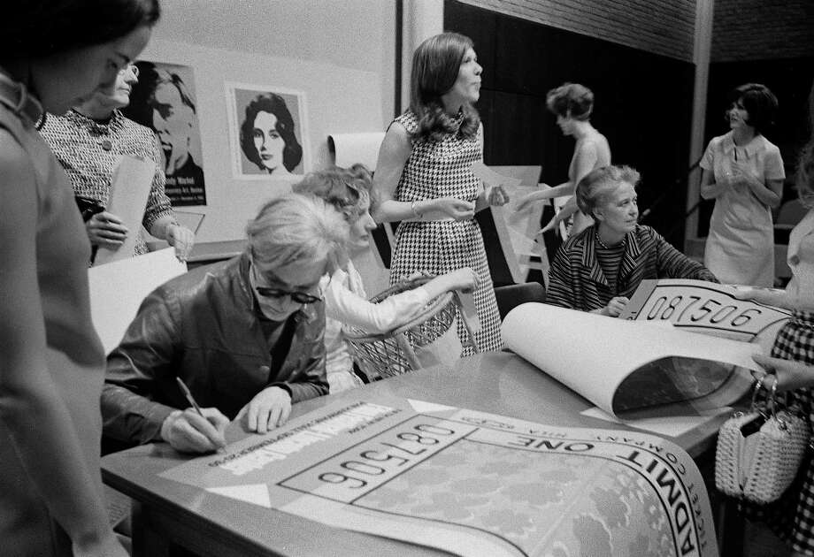 With Dominique de Menil seated beside him, Andy Warhol signs posters at the University of St. Thomas. Photo: Menil Collection Archives / handout book scan