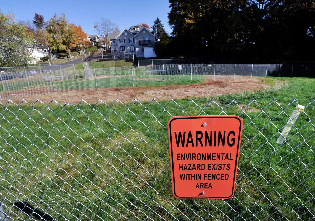 An environmental hazard warning sign posted on a fenced-off area at the William Street field in the Byram section of Greenwich. Sections of the field have been enclosed in fencing and off-limits to the public since April of 2015, when arsenic was found in the soil.