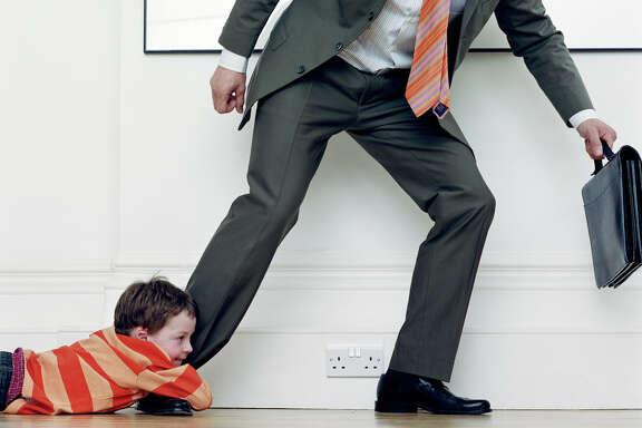Boy (7-9) holding onto businessman's leg