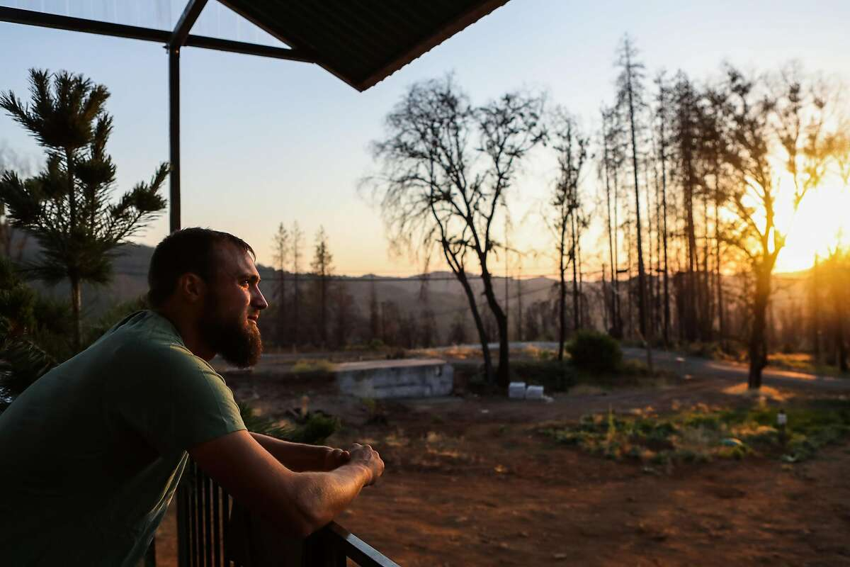 Jake Clouse stands on the porch outside his trailer looking out at the area where he lost his home to the Valley Fire last year, in Cobb, California, on Thursday, Aug. 18, 2016. Jake Clouse lost his home, his two cats, and eight-week-old puppy in fire and has been living in a trailer on the property since.