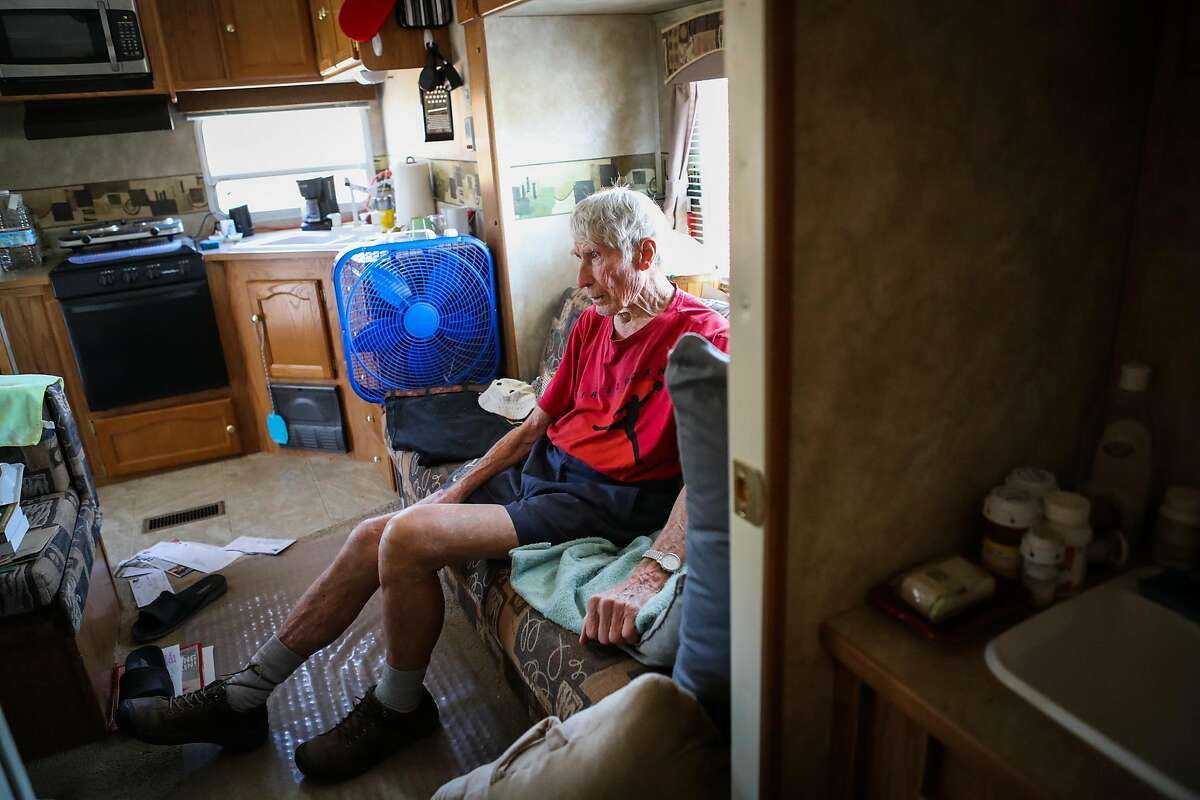 Robert Allen Kraft, 91, a retired physician, watches television in the trailer home he has been living in since his house was destroyed last year in the Valley Fire, in Middletown, California, on Thursday, Aug. 18, 2016.
