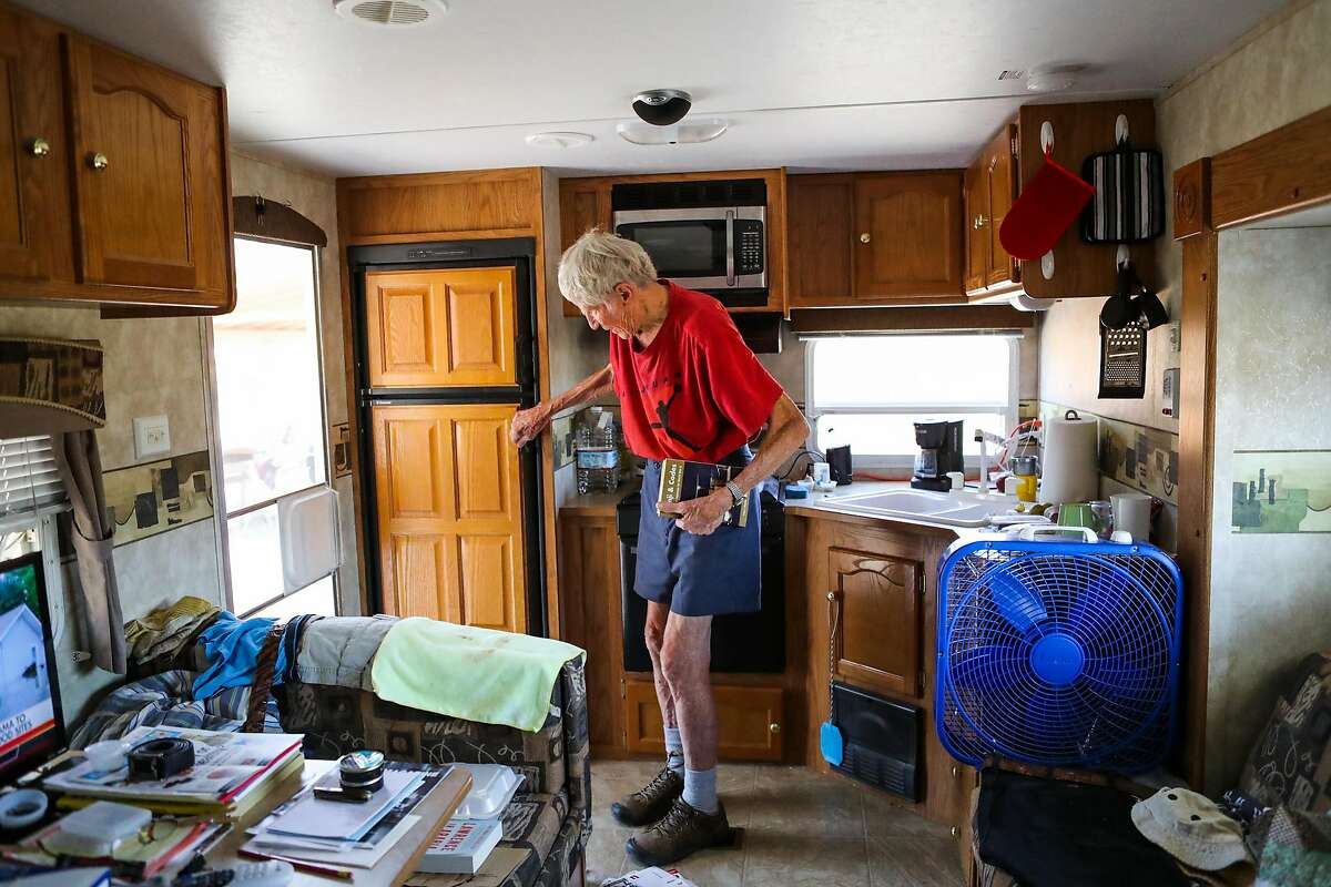Robert Allen Kraft, 91, a retired physician, opens the refrigerator in the trailer home he has been living in since his house was destroyed last year in the Valley Fire, in Middletown, California, on Thursday, Aug. 18, 2016.