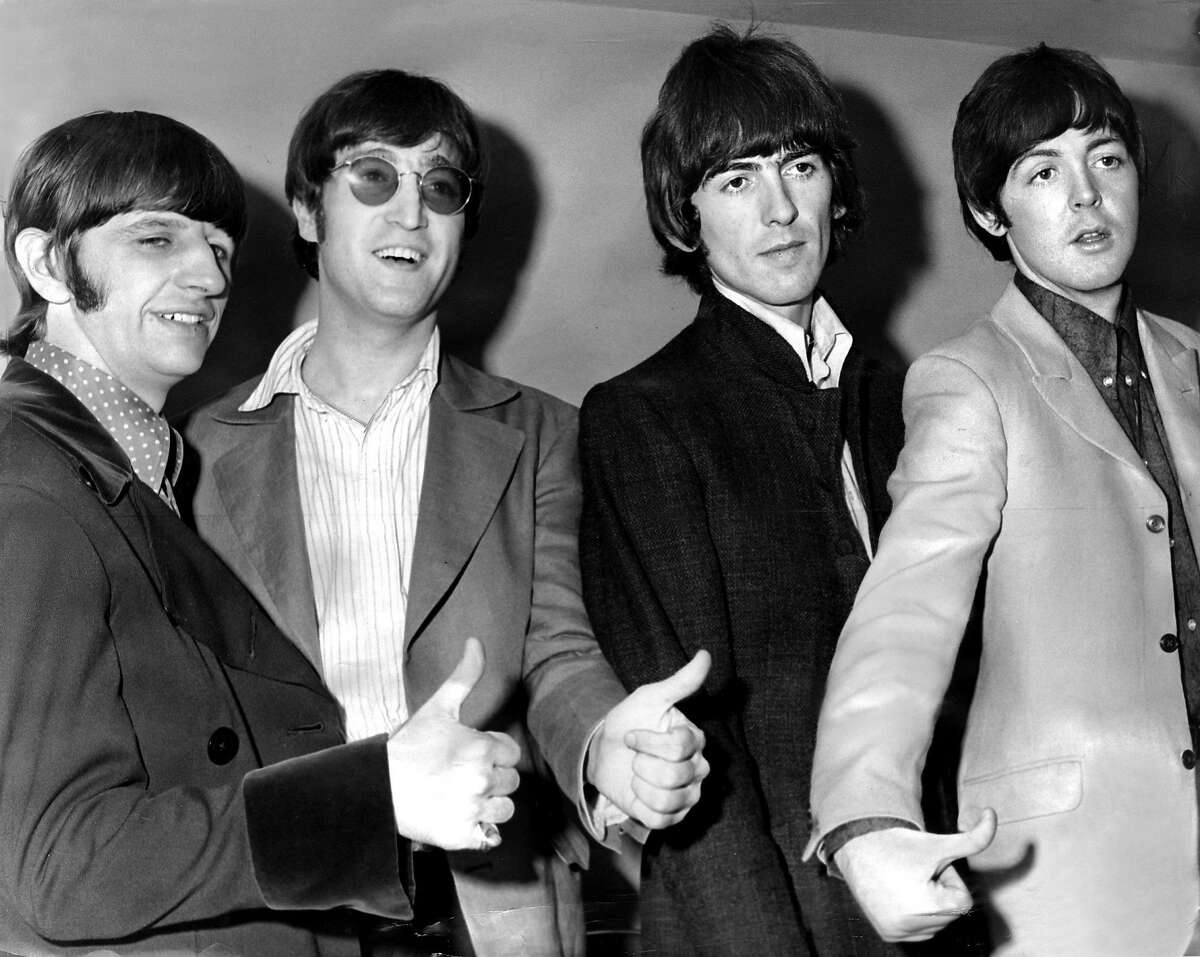 """Beatlemania was in full flower when Ringo Starr, John Lennon, George Harrison and Paul McCartney performed two shows Aug. 25, 1966, at the Seattle Coliseum. This photo was taken at a press conference at which, the P-I reported, """"McCartney whistled, Ringo Starr lighted a cigarette, Lennon in amber-lensed glasses and George Harrison sat blank-faced, responding casually to appeals to smile."""""""