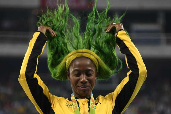 TOPSHOT - Bronze medallist Jamaica's Shelly-Ann Fraser-Pryce fixes her hair on the podium for women's 100m Final at the athletics during the Rio 2016 Olympic Games at the Olympic Stadium in Rio de Janeiro on August 14, 2016.   / AFP PHOTO / Damien MEYERDAMIEN MEYER/AFP/Getty Images