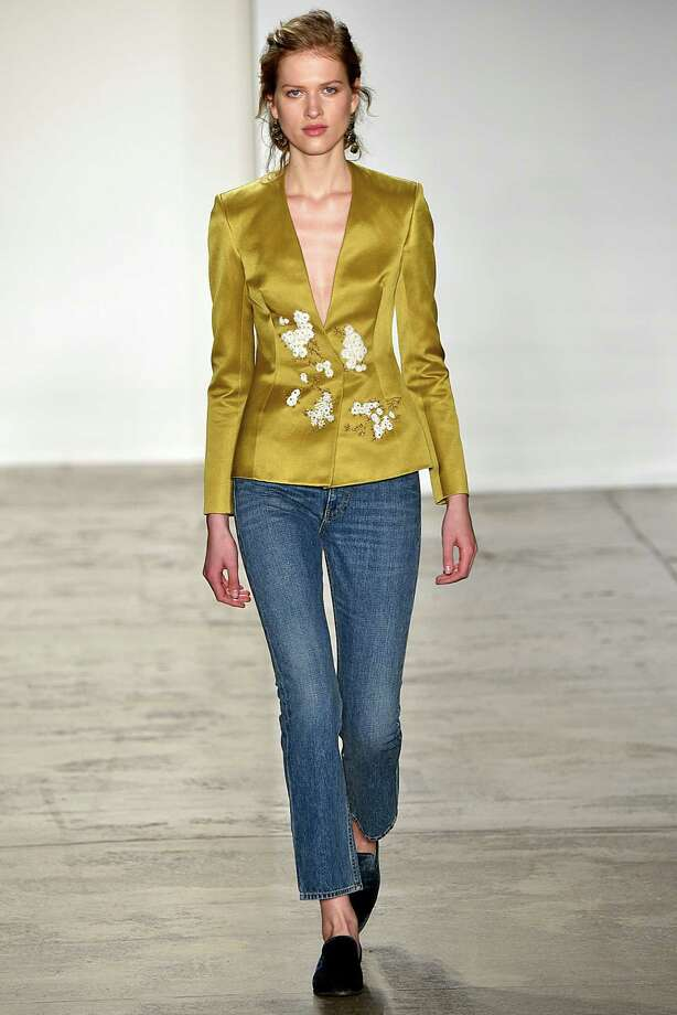 A model wears an embellished satin blouse with denim at the Brock Collection fashion show during Fall/Winter 2016 New York Fashion Week in February. Photo: Victor Virgile / Gamma-Rapho Via Getty Images / Victor VIRGILE /Gamma-Rapho