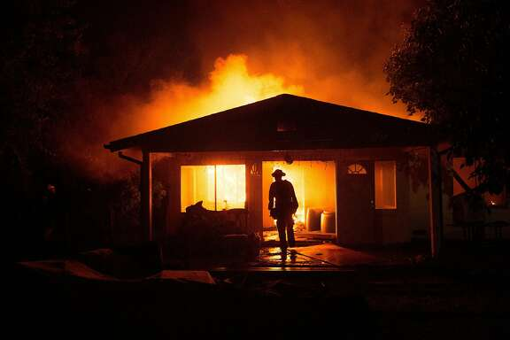 A firefighter approaches a burning residence on Bonham Road as the Clayton Fire burns through Lower Lake, Calif., on Monday, Aug. 15, 2016.