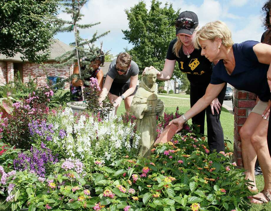 Susan Sales, right, and Amanda Simcoe, second from right, arrange flowers and a statue of St. Francis on the front lawn of the Jabara family's home in Tulsa, Okla., Friday. Photo: Sue Ogrocki, STF / AP2016