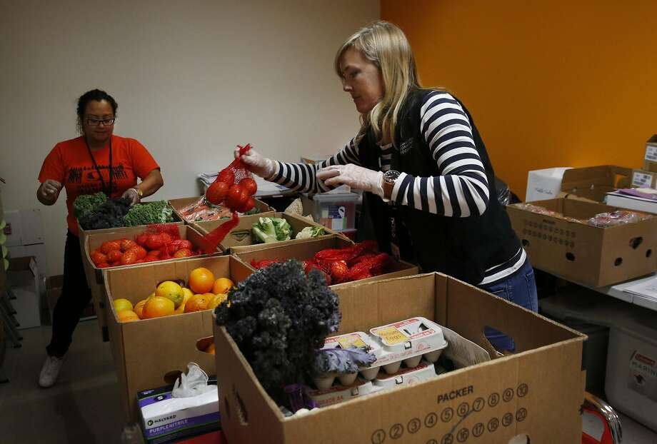 Assistant Martha Orozco (left) and research manager Kate Cheyne, of the Feeding America Intervention Trial for Health: Diabetes Mellitus, assemble food boxes for clients at the Alameda County Community Food Bank. Photo: Leah Millis, The Chronicle