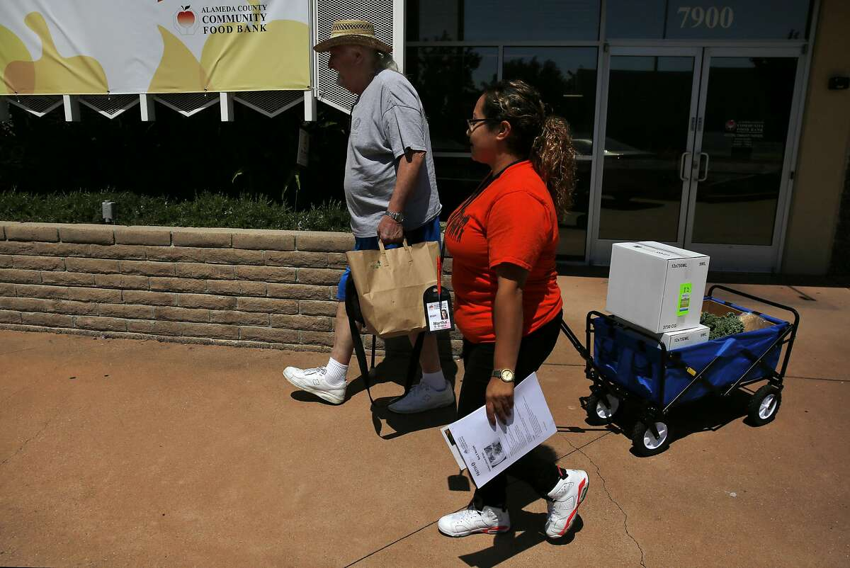 Martha Orozco, right, Research Assistant for Feeding America Intervention Trial for Health�Diabetes Mellitus (FAITH�DM) wheels out food for Ben Goss, 77, who receives it every other week from the Alameda County Community Food Bank June 29, 2016 in Oakland, Calif. The food bank is taking part of a diabetes research trial called Feeding America Intervention Trial for Health � Diabetes Mellitus. The program provides proper food, education and emotional support to food bank clients who struggle with their diabetes.