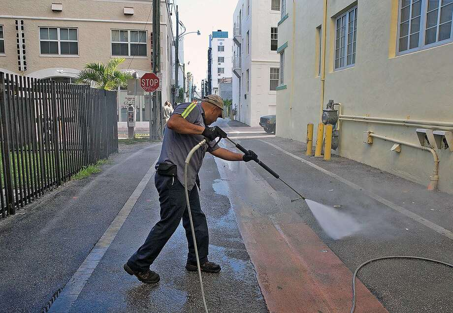 Melvin Gaitan, from the Miami Beach Sanitation Dept., washes down alley ways Friday, Aug. 19, 2016, Miami Beach, Fla., with a high pressure water machine that is set to 250 degrees Fahrenheit, which kills any bacteria or mosquito larvae that could be growing in still waters. (C.M. Guerrero/El Nuevo Herald via AP) Photo: C.M. Guerrero, Associated Press