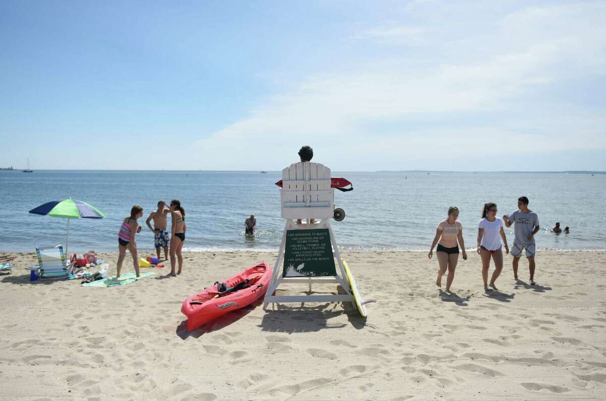 A lifeguard watches over the crowd on the beach at Greenwich Point Park in Old Greenwich, Conn. Sunday, July 3, 2016. Lifeguards are in short supply for the end of summer so bathers are being cautioned to be careful.