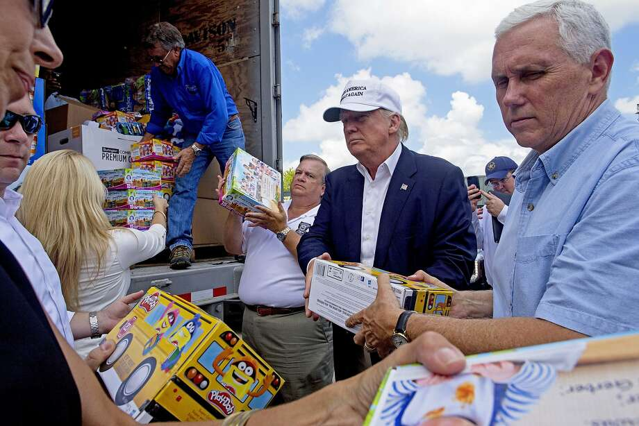 Republican presidential candidate Donald Trump and his running mate, Indiana Gov. Mike Pence, right, help to unload supplies for flood victims during a tour of the flood damaged area in Gonzales, La., Friday, Aug. 19, 2016. (AP Photo/Max Becherer) Photo: Max Becherer, Associated Press