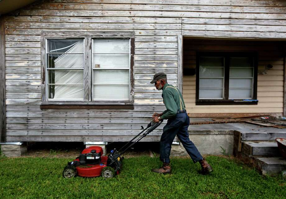 A property owner tends to a lawn along the 3500 block of Hinton Boulevard  in the Independence Heights neighborhood  in northeast Houston. ( Gary Coronado / Houston Chronicle ) Photo: Gary Coronado, Staff / Ã   2015 Houston Chronicle